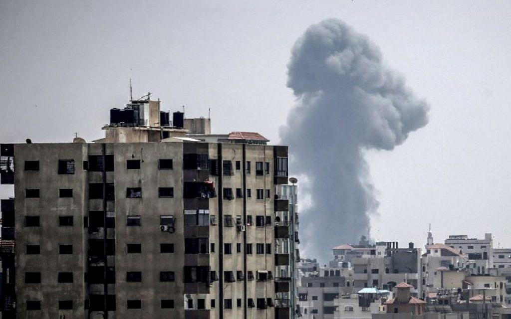 Une fumée s'élève au-dessus des habitations durant des frappes aériennes israéliennes à Gaza City, le 14 juillet 2018 (Crédit : AFP PHOTO / MAHMUD HAMS)