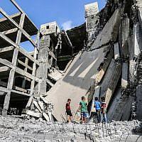 Des petits Palestiniens marchent sur les débris d'un immeuble endommagé par les frappes aériennes israéliennes à Gaza City, le 15 juillet 2018 (Crédit :  AFP / MAHMUD HAMS)