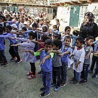 Des enfants palestiniens rassemblés dans la cour d'une école avant la rentrée scolaire, dans le village de Khan al-Ahmar, en Cisjordanie, le 16 juillet 2018. (Crédit : ABBAS MOMANI/AFP)