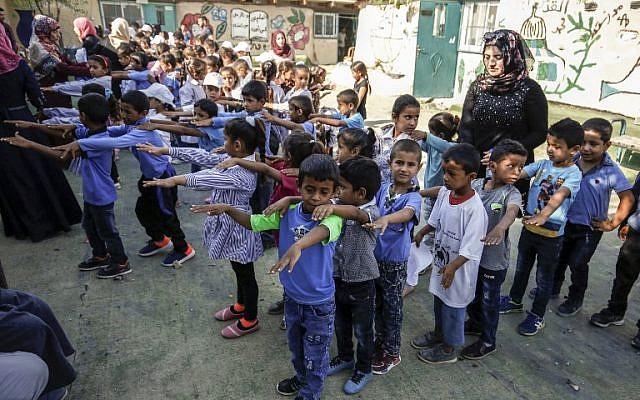 Des enfants rassemblés dans la cour d'une école avant la rentrée scolaire, dans le village de Khan al-Ahmar, en Cisjordanie, le 16 juillet 2018. (Crédit : ABBAS MOMANI/AFP)