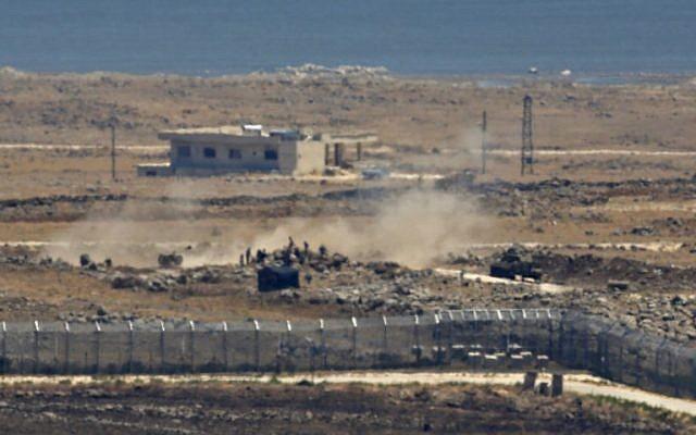 Une photo prise depuis le plateau du Golan israélien montre des rebelles syriens aux côtés d'un tank et d'un canon d'artillerie à proximité de la frontière, dans la province de Quneitra, dans le sud-est de la Syrie, alors que les forces gouvernementales mènent l'assaut, le 16 juillet 2018 (Crédit : AFP Photo/Jalaa Marey)