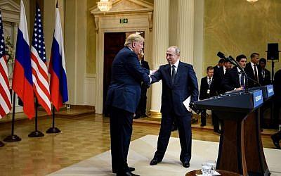 Le président américain Donald Trump, à gauche, et le président russe Vladimir Poutine échangent une poignée de main après une conférence de presse au palais présidentiel finlandais à Helsinki, le 16 juillet 2018 (Crédit : AFP PHOTO / Brendan Smialowski