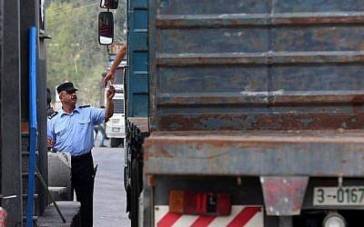Un agent de sécurité palestinien vérifie les papiers d'un chauffeur de camion au point de passage de Kerem Shalom, important des denrées alimentaires dans la bande de Gaza, le 17 juillet 2018. (Crédit : AFP / SAID KHATIB)