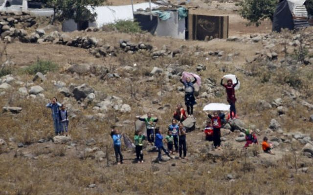 Des civils syriens, déplacés en raison des combats dans le sud-ouest du pays, s'approchent de la barrière frontalière entre la Syrie et Israël, dans le village syrien de Bariqu dans la province de Quneitra, le 17 juillet 2018 (AFP /JALAA MAREY).