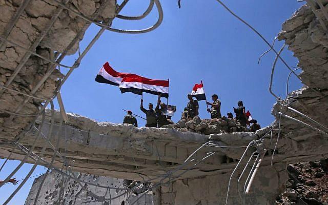 Les forces gouvernementales syriennes brandissent le drapeau national après avoir repris aux rebelles la ville de Quneitra, le 19 juillet 2018 (Crédit : AFP PHOTO / Youssef KARWASHAN)