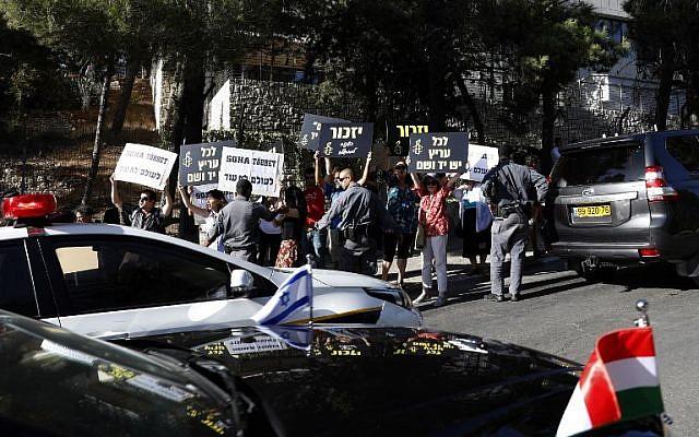 Des manifestants israéliens brandissent des panneaux de l'organisation Amnesty international disant en bloquant la route du convoi transportant le Premier ministre hongrois Viktor Orban au mémorial de la Shoah de Yad Vashem de Jérusalem, le 19 juillet 2018 (Crédit : AFP PHOTO / GALI TIBBON)