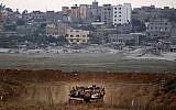 Un tank de combat israélien Merkava patrouille le long de la frontière avec la bande de Gaza à proximité du kibboutz Nahal Oz dans le sud d'Israël. (Crédit :  AFP Photo/Jack Guez)