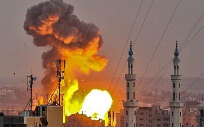 Une boule de feu explose dans Gaza City pendant une frappe israélienne (Crédit : AFP / BASHAR TALEB)
