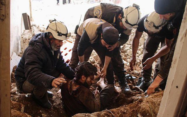 Des membres de la protection civile syrienne, également connus sous le nom de Casques blancs, sortent une victime des décombres de sa maison à la suite d'une attaque aérienne des forces gouvernementales dans une zone tenue par les rebelles dans la ville de Daraa, dans le sud de la Syrie, le 8 avril 2017. (Mohamad ABAZEED/AFP)