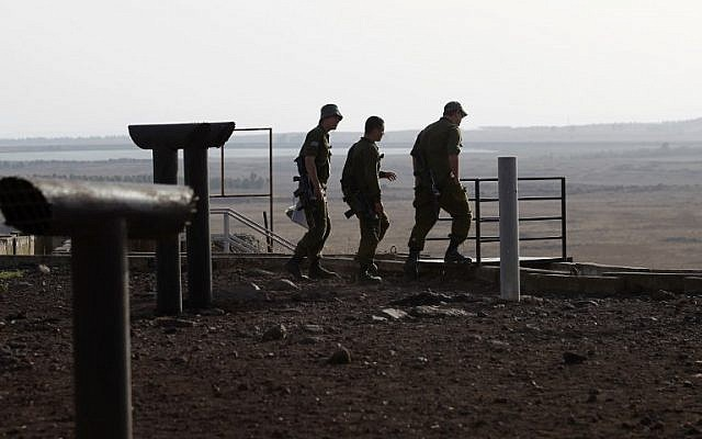 Des soldats israéliens sur la colline Tel Saki, sur le plateau du Golan annexé par Israël, de l'autre côté de la frontière de la province de Deraa en Syrie, le 24 juillet 2018 (Crédit :  / AFP PHOTO / JALAA MAREY)