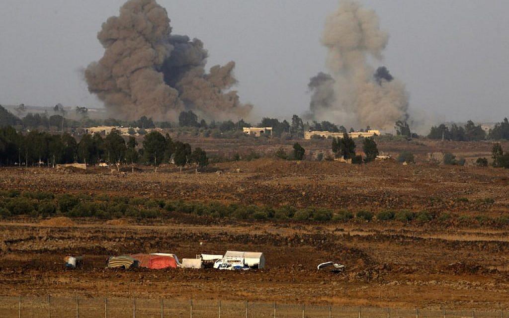 Une photo prise le 24 juillet 2018 depuis la colline Tal Saki sur le plateau du Golan montre de la fumée s'élevant au-dessus des bâtiments de l'autre côté de la frontière syrienne lors de frappes aériennes soutenant une offensive menée par le gouvernement syrien dans la province de Daraa, dans le sud-ouest de la province de Daraa. (AFP/JALAA MAREY)
