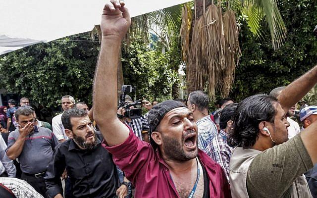Des Palestiniens manifestent contre les réductions de postes annoncées par l'agence - plus de 250 - suite à la réduction des fonds versés par les Etats-Unis, au siège de l'agence à Gaza City, le 25 juillet 2018  (Crédit : SAID KHATIB / AFP)