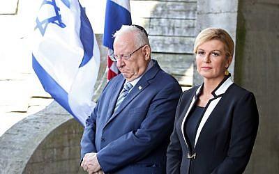 Le président israélien Reuven Rivlin (à droite) et la présidente croate Kolinda Grabar Kitarovic rendent hommage au mémorial en forme de fleur aux victimes du camp de concentration de Jasenovac, démantelé il y a 73 ans à Jasenovac, le 25 juillet 2018. (Crédit : AFP / STRINGER)