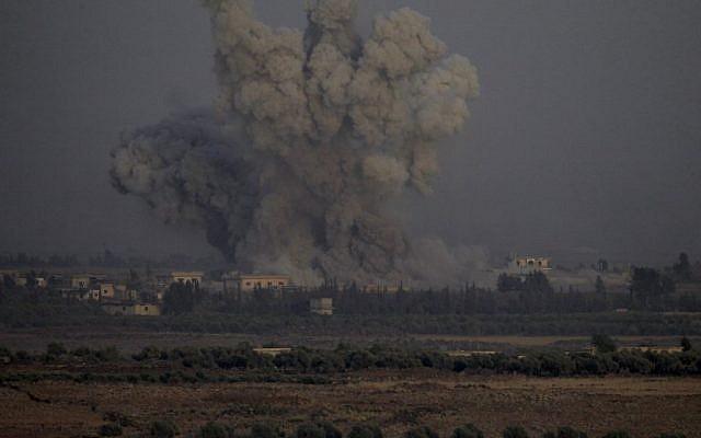 Une photo prise le 25 juillet 2018 depuis la colline Tal Saki sur les hauteurs du Golan montre de la fumée s'élevant au-dessus des bâtiments de l'autre côté de la frontière syrienne lors de frappes aériennes soutenant une offensive menée par le gouvernement syrien dans la province méridionale de Quneitra. (AFP / JALAA MAREY)