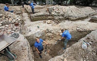 Des membres d'une équipe internationale d'archéologues travaillent à dégager des parties de la Grande Synagogue de Vilnius le 25 juillet 2018. (Crédit : AFP/Petras Malukas)