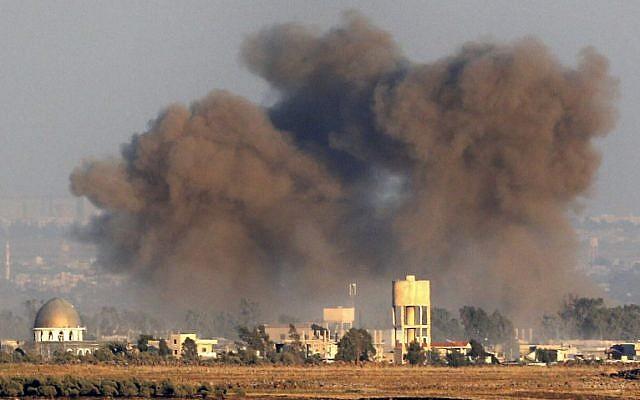 Une photo prise le 26 juillet 2018, près du kibboutz Ein Zivan sur les hauteurs du Golan israélien, montre de la fumée s'élevant au-dessus des bâtiments de l'autre côté de la frontière syrienne lors de frappes aériennes soutenant une offensive menée par le gouvernement dans la province de Quneitra, au sud du pays. (AFP Photo/Jack Guez)