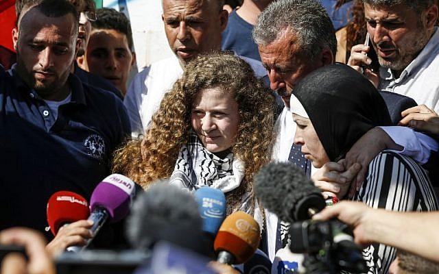 La militante palestinienne Ahed Tamimi, au centre, parle aux journalistes à sa sortie de prison après une pine de huit mois pour avoir giflé des soldats israéliens, accompagnée de son père (au centre-droit) et de sa mère (à droite), à Nabi Saleh, en Cisjordanie, le 29 juillet 2018 (Crédit :  / AFP PHOTO / ABBAS MOMANI)