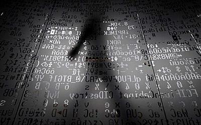 Une photo prise le 17 octobre 2016 montre un employé marchant derrière un mur de verre avec des symboles codés par machine au siège du géant de la sécurité Internet Kaspersky à Moscou. (AFP/Kirill KUDRYAVTSEV)