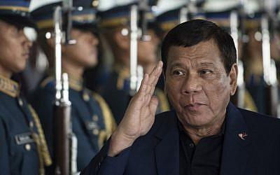 Le président philippin Rodrigo Duterte passe en revue la garde d'honneur alors qu'il arrive à l'aéroport international de Manille le 24 mai 2017. (AFP/Noel Celis)