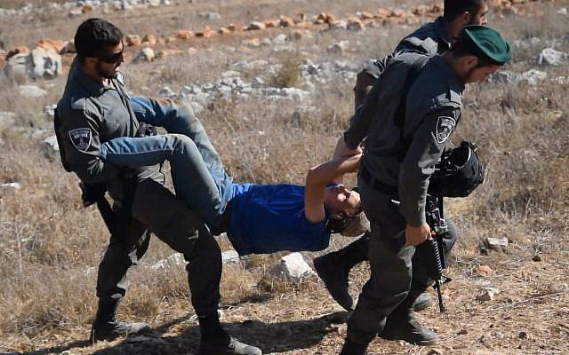 """Photo d'illustration : La police des frontières emmène un membre des """"jeunes des collines"""" durant l'évacuation d'un avant-poste illégal dans le nord de la Cisjordanie (Crédit: Zman Emet, Kan 11)"""