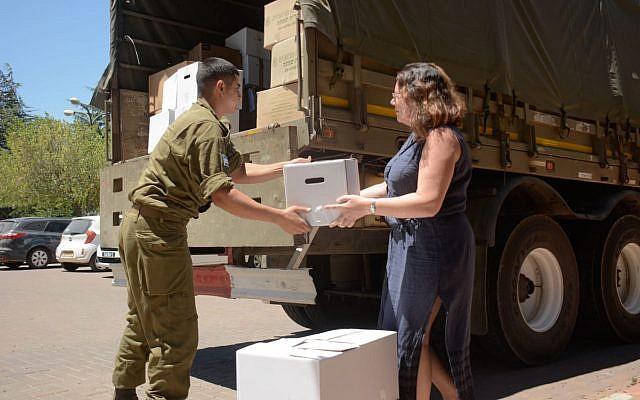 Des habitants du Golan israélien remettent à Tsahal des colis pour les Syriens déplacés fuyant la guerre civile en Syrie, en juillet 2018. (Armée israélienne)