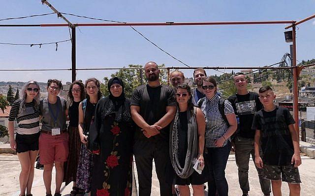Des militants de gauche d'un groupe Birthright qui ont mis en scène un départ du mouvement, avec une famille qui risque l'évacuation à cause de la démolition de son village à Jérusalem Est, le 15 juillet 2018. (Autorisation)