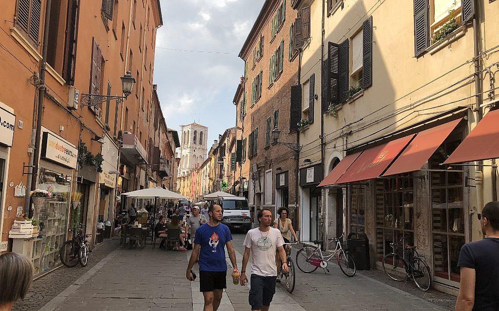 Via Mazzini, l'une des principales rues du centre ville de Ferrare, en Italie, qui faisait autrefois partie du ghetto. On peut voir le clocher de la cathédrale en arrière-plan, et le bâtiment de la synagogue en rénovation se trouve derrière le camion. (Rossella Tercatin/ Times of Israel)