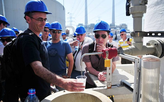 Les visiteurs remplissent leurs verres avec de l'eau de mer traitée dans une usine de dessalement près de Hadera, en Israël (Crédit : Shay Levy / Flash90)