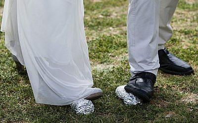 La mariée Lin Dror (G) et le marié Alon Marcus (D) cassent deux verres à la fin de leur cérémonie de mariage juif réformé célébré devant la Knesset, à Jérusalem, le 18 mars 2013, pour protester contre le monopole du Rabbinat orthodoxe sur les certificats de mariage et l'absence de mariages civils en Israël. (Flash 90)