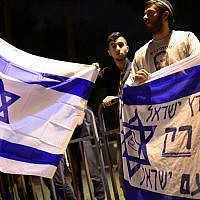 """Des militants de droite israéliens protestent aux abords d'une cérémonie conjointe pour les familles de victimes israéliennes et palestiniennes lors de la Journée israélienne de commémoration, le 21 avril 2015 Le drapeau dit : """"La terre d'Israël pour les Israéliens seulement"""" (Crédit : Tomer NeubergFlash90)"""