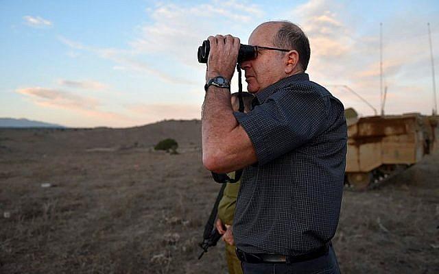 Le ministre de la Défense de l'époque, Moshe Yaalon, regarde à travers des jumelles lors d'une visite dans le cadre d'un exercice militaire du Corps des blindés, sur les hauteurs du Golan, le 22 octobre 2015. (Ariel Hermoni/Ministère de la Défense)