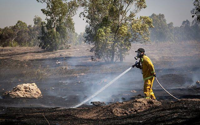 Les pompiers éteignent un incendie dans un champ allumé par des des combustibles attachés à des cerfs-volants envoyés depuis la bande de Gaza par des Palestiniens, le 27 juin 2018 (Crédit : Flash90)