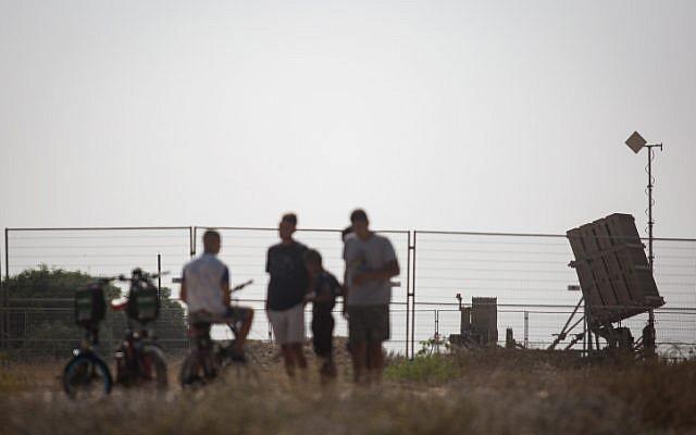 Des Israéliens regardent une batterie de défense antimissile du Dôme de fer dans le sud d'Israël, le 14 juillet 2018 (Crédit : Hadas Parush/Flash90)