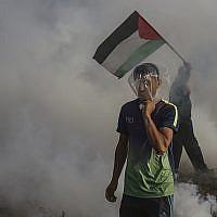 Des gaz lacrymogènes lancés par les troupes israéliennes retombent sur des Palestiniens durant une manifestation à la frontière entre Israël et Gaza, le 13 juillet 2018 (Crédit : Wissam Nassar/Flash90)