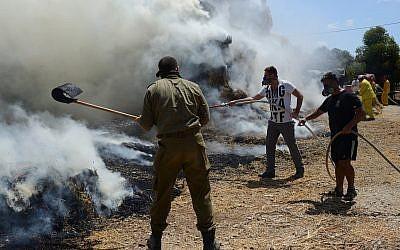Les pompiers israéliens et les équipes de sécurité luttent contre un incendie près d'un élevage de bovins, allumé par un dispositif incendiaire lancé depuis la bande de Gaza au  Kibbutz Nahal-Oz, le 21 juillet 2018 (Crédit :  Gili Yaari/FLASH90)
