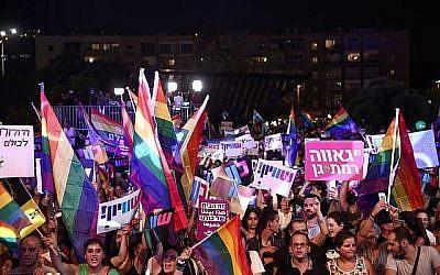 Des membres de la communauté LGBT et des sympathisants participent à une manifestation contre un amendement de la Knesset refusant la gestation pour autrui pour les couples gays, sur la place Rabin à Tel Aviv le 22 juillet 2018. (Crédit : Miriam Alster / Flash90)