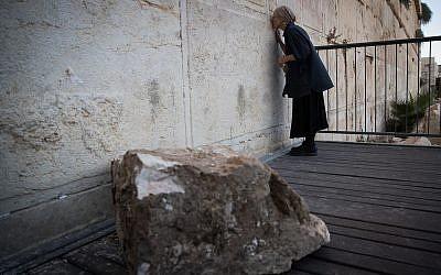 Daniella Goldberg se tient à côté de la grosse pierre qui a chuté sdu mur Occidental, dans la Vieille ville de Jérusalem, dans la section de prière mixte, le 23 juillet 2018 (Crédit  : Yonatan Sindel/Flash90)