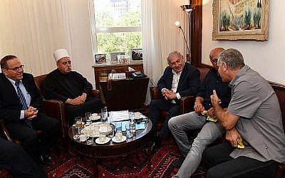 Le Premier ministre Benjamin Netanyahu, au centre, rencontre Sheikh Muafak Tariff,  leader spirituel de la communauté druze d'Israël, le ministre des communications  Ayoub Kara, à gauche, et d'autres leaders druzes à son bureau de Jérusalem pour évoquer la loi sur l'Etat-nation, le 27 juillet 2018 (Crédit : Kobi Gideon/GPO/Flash90)