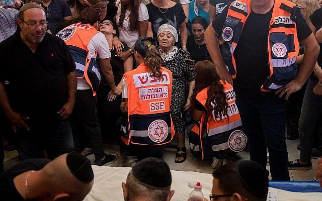 Des amis et des membres de la famille pleurent lors des funérailles de Yotam Ovadia, 31 ans, au cimetière Har Hamenuchot, à Jérusalem, le 27 juillet 2018. Ovadia a été assassiné près de chez lui dans l'implantation d'Adam lorsqu'un adolescent palestinien l'a poignardé et blessé deux autres Juifs lors d'une attaque terroriste le 26 juillet 2018. (Yonatan Sindel/Flash90)