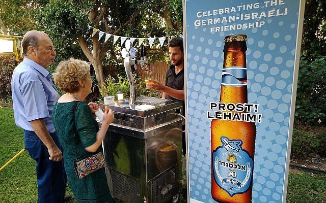 """Des invités goûtent la nouvelle bière germano-israélienne appelée """"70"""" à la résidence de l'ambassadeur allemand en Israël Clemens von Goetze à Herzliya, le 19 juillet 2018 (Crédit : Raphael Ahren/TOI)"""