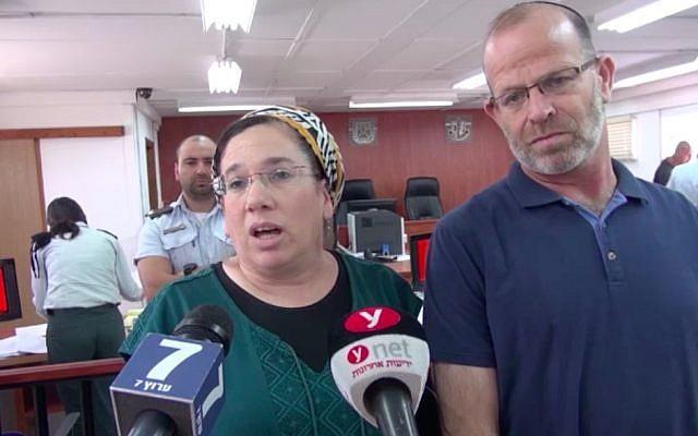 Nirit Zamoraà à gauche, parle aux journalistes dans la salle du tribunal militaire de Judée aux côtés de son mari avant la condamnation de son agresseur, le 16 juillet 2018 (Capture d'écran/Israel National News)