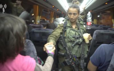 """Des soldats de Tsahal donnent de l'eau aux secouristes de l'organisation """"Casques Blancs"""" et à leurs familles, qu'Israël a acheminés de Syrie en Jordanie, alors qu'ils fuyaient le régime d'Assad, le 22 juillet 2018. (Armée israélienne)"""