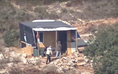 Un groupe d'habitants retournent vers un avant-poste situé aux abords de l'implantations de Talmon, en Cisjordanie, après une attaque présumée contre des Palestiniens locaux (Crédit : YouTube/ Haaretz)