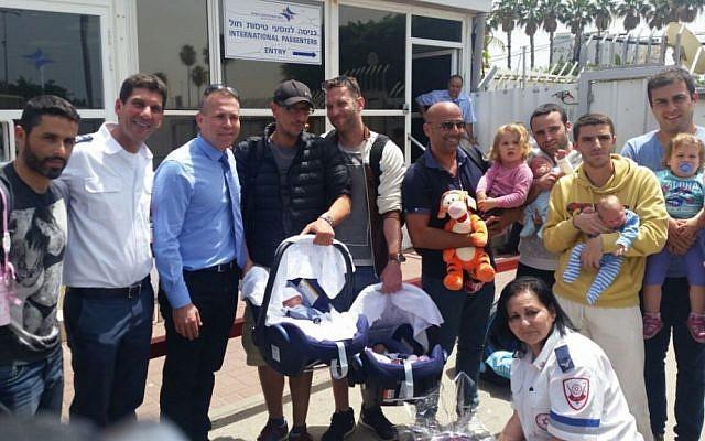 Illustration : les pères de bébés nés de mères porteuses népalaises et conduits en Israël le 27 avril 2015 posent avec le directeur général du Magen David Adom, Eli Bin (deuxième à partir de la gauche) et le ministre de l'Intérieur Gilad Erdan (troisième à partir de la gauche). (Crédit : avec l'aimable autorisation du MDA)