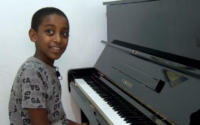 'Oshri Bitau, et son nouveau piano, dans sa maison de Nazareth Illit, le 15 juillet 2018. ( Crédit : capture d'écran Hadashot)