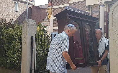 Tom Furstenberg, à droite, et membre de la communauté juive de Deventer transporte une arche à Torah hors de l'ancienne synagogue qu'il s'apprête à quitter, le 30 juillet 2018  Crédit : Cnaan Liphshiz/JTA)