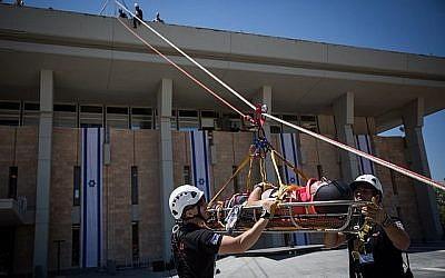 Des membres de la Garde d'honneur de la Knesset, des pompiers, de l'armée de défense israélienne, de la police israélienne et du Magen David Adom Emergency Medical Services participent à un exercice d'urgence simulant un tremblement de terre à la Knesset, Jérusalem, 13 juin 2017. (Hadas Parush / Flash90)