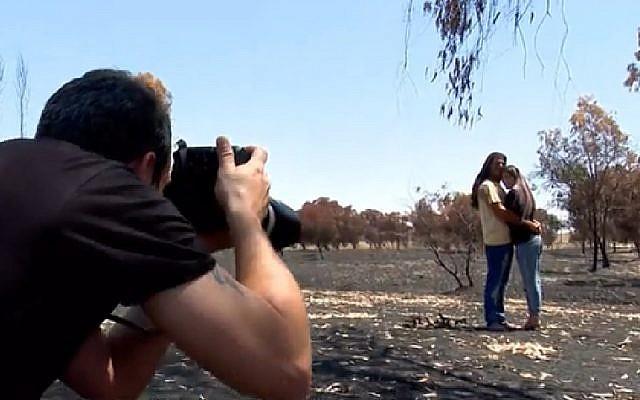 Un photographe prend un cliché de Dana et Itai Nisanov parmi les arbres brûlés à proximité de la frontière avec Gaza (Capture d'écran : Hadashot news)
