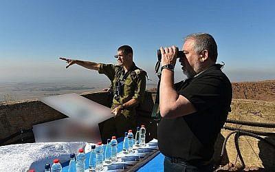 Le ministre de la Défense, Avigdor Liberman, observe avec ses jumelles au sommet d'une colline surplombant la frontière syrienne, alors que le général de brigade Amit Fisher lui fait un exposé sur l'évolution de la situation dans la région, le 10 juillet 2018. (Ariel Hermoni/Ministère de la Défense)