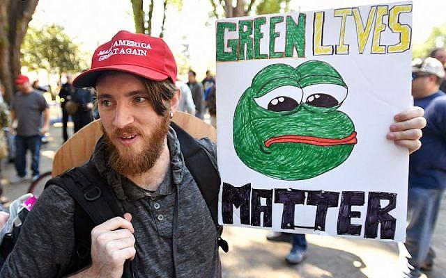 Un homme brandit une pancarte avec une image de Pepe the frog à un rassemblement à   Berkeley, en Californie, le 27 avril 2017 (Crédit :  Josh Edelson/AFP/Getty Images)